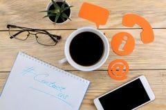 Cli?ntondersteunende dienst Contacteer ons voor terugkoppelen De Desktop met blocnote, smartphone en de glazen en divers koppelen stock fotografie