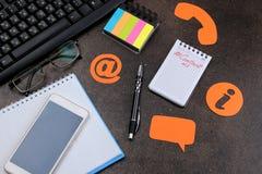Cli?ntondersteunende dienst Contacteer ons voor terugkoppelen De Desktop met blocnote, smartphone en de glazen en divers koppelen stock afbeeldingen