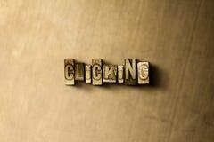 CLICCARE - il primo piano dell'annata grungy ha composto la parola sul contesto del metallo Immagine Stock