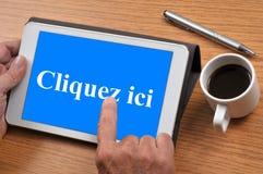 Clicchi qui scritto in francese su una compressa immagine stock libera da diritti