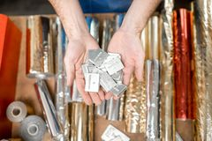 Cliche for stamping with foil. Holding a pile of small metal cliche for stamping with foil at the printing manufacturing Stock Image