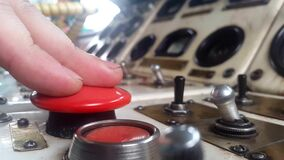 Click on the big red button. This stock video features a white control panel with lots of toggle switches and black buttons. A hand reaches over to press a black
