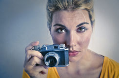 Click. A blonde woman holding an old-fashioned camera in her hands stock photography