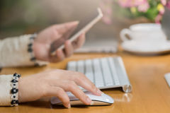 Click and connect ,bokeh and blurred background. Close-up of business executive woman hands clicking mouse computer and using smart phone,Click and connect royalty free stock photography