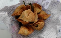 Tasty Samosas. A Click of Delicious Indian snack food Samosas with fried chillies unpacked from paper bag stock photography