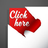 `Click here` text uncovered from torn paper corner. Stock Photography
