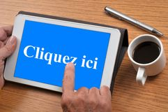 Click here written in French on a tablet. Connection concept with a tablet with a cup of coffee royalty free stock image