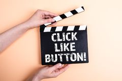 Click like button. Female hands holding movie clapper.  royalty free stock images