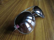 Oval shape shades. A click of oval shaped sun goggles placed on a table and diffused sun light reflecting in from the windows royalty free stock photos