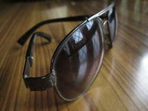 Oval shape shades. A click of oval shaped sun goggles placed on a table and diffused sun light reflecting in from the windows stock photography