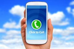 Click to call concept. Hand with phone over blue sky background stock photography