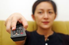 Click TV Remote. A Chinese lady clicking the TV remote, shallow focus royalty free stock images