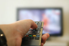 Clicking Television Remote Control. Image of a hand clicking TV Remote Control with out of focus television in the background Stock Photos