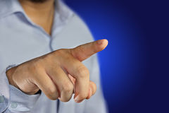 Clicking virtual display. Young man pointing his finger to click virtual display against blue background Royalty Free Stock Photo