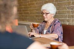 Client à l'aide de l'ordinateur portable tout en ayant le café en café Image stock