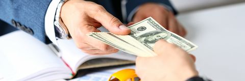 Client arm give pack of hundred dollars bills. To manager as insurance payment closeup. Driver loss prevention, take fee, secure road trip pay, harmless drive Royalty Free Stock Image