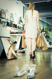 Client with bags of purchases is walking. Around the shoes store Royalty Free Stock Image