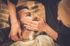 Client in barber shop. Client during beard shaving in barber shop Royalty Free Stock Photography