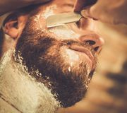 Client during beard shaving Royalty Free Stock Image