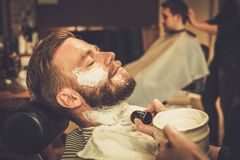 Client during beard shaving. In barber shop Royalty Free Stock Photography