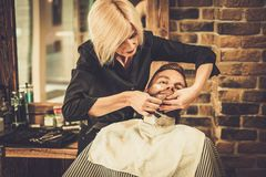 Client during beard shaving Royalty Free Stock Photo
