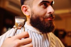 Barber is shaping his beard to the client in barbershop stock photo