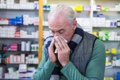 Client couvrant son nez de mouchoir tout en éternuant Images stock