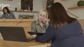 Client de consultation de conseiller financier féminin en café banque de vidéos