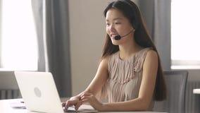 Client de consultation de port de casque de réceptionniste asiatique de femme d'affaires sur l'ordinateur portable clips vidéos