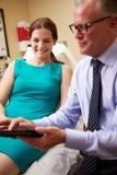 Client de Discussing Proceedure With de chirurgien cosmétique dans le bureau photographie stock