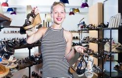 Client de femelle adulte tenant beaucoup de paires de chaussures photos stock