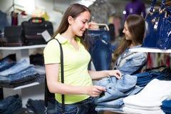 Client de femme choisissant des jeans à la boutique Images stock