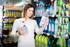 Client de fille recherchant des décapants pour la maison dans le supermarché photographie stock