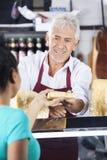 Client de Giving Cheese To de vendeur au compteur dans le supermarché image stock