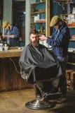 Client de hippie obtenant la coupe de cheveux Coiffeur avec des cheveux de r?glage de tondeuse sur le temple du client Le coiffeu photos libres de droits