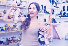 Client de jeune femme tenant beaucoup de paires de chaussures Images stock