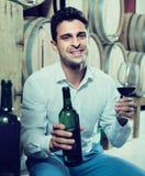 Client de sourire d'homme tenant le verre et la bouteille de vin Photo stock