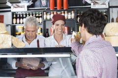 Client de sourire de Serving Cheese To de vendeuse dans la boutique Photographie stock libre de droits