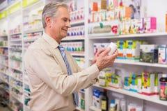 Client de sourire regardant la médecine Photo stock