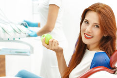Client in the dental chair. Holding an apple Stock Images