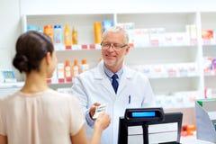 Client donnant l'argent au pharmacien à la pharmacie photo stock