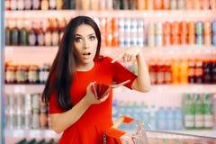 Client drôle vérifiant son portefeuille dans un magasin image stock