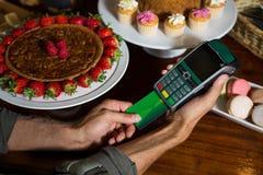 Client effectuant le paiement par la carte de crédit au compteur image stock