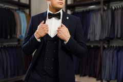 Client is elegant guy trying on a suit in a mirror shop. In the background classic suits and jackets. Perfect to the last detail. Modern businessman. Fashion Stock Images