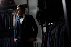 Client is elegant guy trying on a suit in a mirror shop. In the background classic suits and jackets. Perfect to the last detail. Modern businessman. Fashion Stock Photo