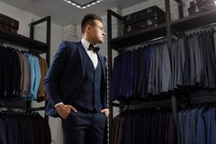 Client is elegant guy trying on a suit in a mirror shop. In the background classic suits and jackets. Perfect to the last detail. Modern businessman. Fashion Royalty Free Stock Photo