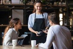 Client en café payant utilisant le paiement mobile de NFC d'application image stock