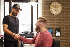 Client et coiffeur se serrant la main au raseur-coiffeur Photos libres de droits