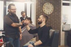 Client et coiffeur se serrant la main au raseur-coiffeur Photos stock