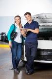 Client et mécanicien heureux With Digital Tablet dedans Images stock